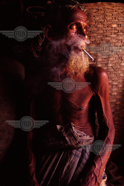 Headman of a rice farming household sits, smoking a cigarette, backed by sacks and storage baskets of rice.