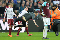 Ashley Barnes of Burnley tackles a fan during a pitch invasion during West Ham United vs Burnley, Premier League Football at The London Stadium on 10th March 2018