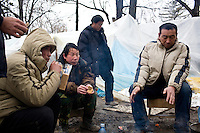 ROMANIA / Bucharest / 22.02.09..Chinese immigrants warm themselves around a fire across the street from the Chinese Embassy...Hundreds of Chinese immigrants are currently stuck in Romania after their work contracts with construction firms here were suddenly terminated in late January. They expected to make at least 800 Euros per month, or double what they can make in China as agricultural laborers. About 80 of them are camped out under plastic sheeting in front of the Chinese Embassy hoping to get some kind of help. During the day, hundreds more are joining them to stage a protest. They paid a Chinese broker 10,000 Euros a piece for the lucrative four year construction contracts and are hoping to get reimbursed in order to be able to buy tickets home. The immigrants are relying upon the help of generous Romanians who pull up and deliver food from their cars. The economic crisis hit Romania just as many of the immigrants arrived in November. ..© Davin Ellicson / Anzenberger