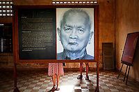 "Tourists are seen behind a portrait of former Khmer Rouge leader ""Brother Number two"" Nuon Chea as they read about him at the former notorious Tuol Sleng prison that is now the Genocide Museum in Phnom Penh August 5, 2014. Cambodia's young population is very aware of its grim history, with almost every family suffering losses. Most Cambodians still want justice and to see the U.N.-backed court find the recalcitrant Nuon Chea, Pol Pot's right-hand man, and ex-President Khieu Samphan, guilty of crimes against humanity, but the court has been mired in disputes, resignations, funding shortages and accusations of political interference and has to date delivered just one verdict. The court will deliver verdicts for Noun Chea and Khieu Samphan on August 7, 2014. Picture taken August 5, 2014. REUTERS/Damir Sagolj (CAMBODIA)"