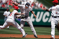 LOS ANGELES,CA - APRIL11,2009:  Los Angeles Angels third baseman Chone Figgins, left, tags out Boston Red Sox Jacoby Ellsbury during a run down between second and third base in 1st inning action of baseball game in Anaheim, California April 11, 2009. Angels Erick Aybar, right.