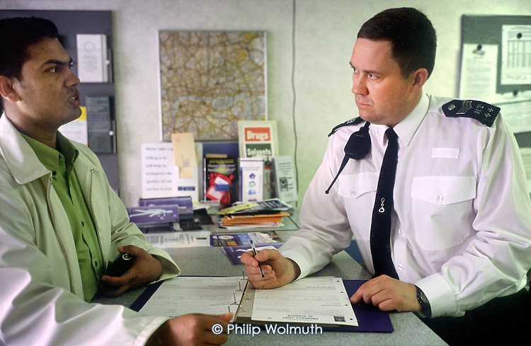 Sergeant Simpson deals with an enquiry at Brick Lane Police Office in Tower Hamlets, London.