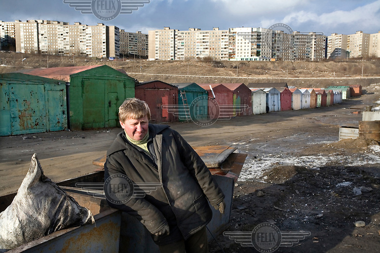 A local man outside rows of garages near apartment blocks in the city. The local men of Murmansk have an unlikely passion - they love escaping to their garages, which are often built far away from the apartment blocks where they live, to fix their cars, relax and socialise. A resident explains, 'They call them seashells. I don't know why because they are so ugly and seashells are so pretty.'