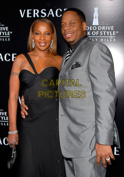 MARY J. BLIGE & GUEST.Attends The Rodeo Drive Walk Of Style Award honoring Gianni and Donatella Versace held at The Beverly Hills City Hall in Beverly Hills, California, USA,.February 08 2007..half length black dress one shoulder strap gown tatoos.CAP/DVS.©Debbie VanStory/Capital Pictures