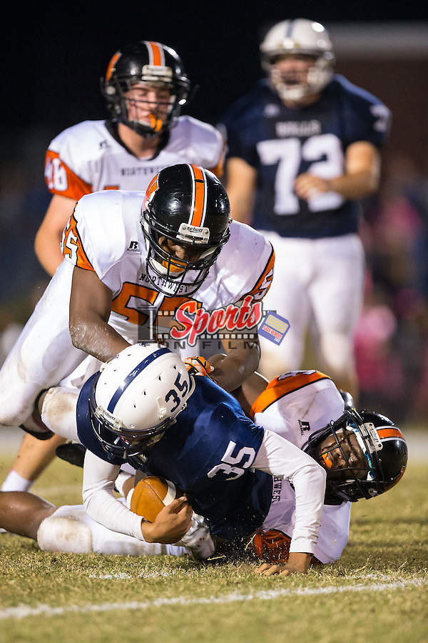 Remington Peters (35) of the Hickory Ridge Ragin' Bulls is tackled from behind by Darian Goolsby (16) and Daekwon Smith (55) of the Northwest Cabarrus Trojans at Hickory Ridge High School on October 17, 2014 in Harrisburg, North Carolina.  The Ragin' Bulls defeated the Trojans 34-6.  (Brian Westerholt/Sports On Film)
