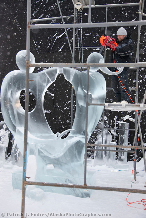 "Russian sculptor Sergei Loginov, carves away on a single block, abstract sculpture titled ""Adam and Eve: One Heart for Two"" during the 2009 World Ice Art Championships in Fairbanks, Alaska."