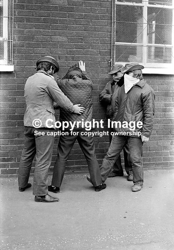 Ulster Defence Association (UDA) members search a passer-by in the Woodvale district of Belfast, N Ireland, UK. Masked. NI Troubles. Ref: 19720514001...Copyright Image from Victor Patterson, 54 Dorchester Park, Belfast, UK, BT9 6RJ..Tel: +44 28 9066 1296.Mob: +44 7802 353836.Voicemail +44 20 8816 7153.Skype: victorpattersonbelfast.Email: victorpatterson@mac.com.Email: victorpatterson@ireland.com (back-up)..IMPORTANT: If you wish to use this image or any other of my images please go to www.victorpatterson.com and click on the Terms & Conditions. Then contact me by email or phone with the reference number(s) of the image(s) concerned.