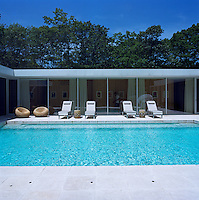 Sun-loungers lined up against the glass wall which lines the main corridor to the house, overlook the swimming pool