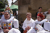 Women at the procession, dressed in traditional Moravian costumes.<br /> <br /> Twelve-year-old Frantisek Libosvar dressed as a girl and with a rose in his mouth leads the royal procession during Ride of the Kings as part of Navalis Celebrations on May 15, 2015 in Prague, Czech Republic. The Navalis Saint John's celebrations take place to commemorate Czech saint and Prague native, Saint John of Nepomuk, patron of all people of the water. <br /> <br /> <br /> The Ride of the Kings takes place during the spring, as a part of the Pentecost traditions . A group of young men ride through a Prague in a ceremonial procession. The ride is headed by chanters, followed by pageboys with unsheathed sabres who guard the King &ndash; a young boy with his face partially covered, holding a rose in his mouth &ndash; and the rest of the royal cavalcade. The King and pageboys are dressed in women&rsquo;s ceremonial costumes, while the other riders are dressed as men. The entourage rides on decorated horses, stopping to chant short rhymes that comment humorously on the character and conduct of spectators. The chanters receive donations for their performance, placed either in a money box or directly into the riders&rsquo; boots. The King&rsquo;s retinue returns home after a few hours of riding, and celebrates in the evening at the house of the King with a small feast, music and dancing. The practices and responsibilities of the Ride of the Kings are transmitted from generation to generation. The traditional paper decorations for the horses and the ceremonial costumes, in particular, are made by women and girls familiar with the processes, colour patterns and shapes specific to each village