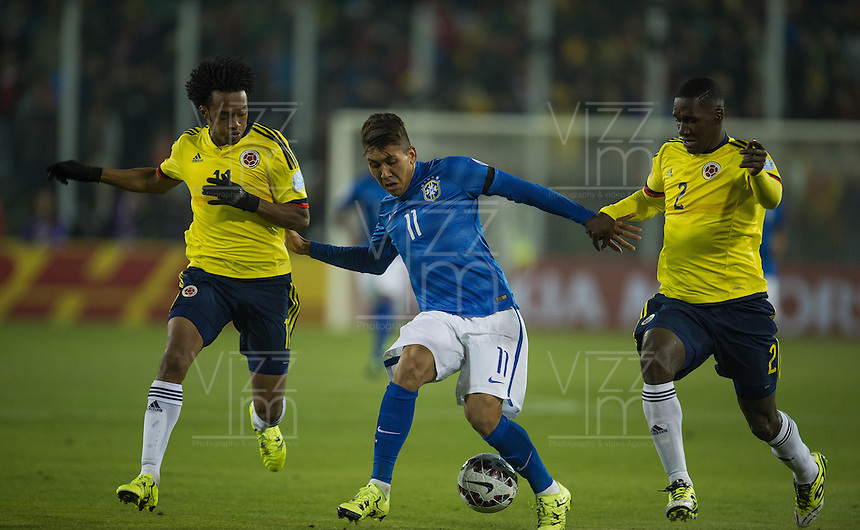 SANTIAGO DE CHILE- CHILE - 17-04-2015: Cristian Zapata (Der.) y Juan G Cuadrado (Izq.) jugadores de Colombia, disputan el balón con Roberto Firmino (Cent.) jugador de Brasil durante partido Colombia y Brasil, por la fase de grupos, Grupo C, de la Copa America Chile 2015, en el estadio Monumental en la Ciudad de Santiago de Chile. / Cristian Zapata (R) and Juan G Cuadrado (L) players of Colombia, vies for the ball with Roberto Firmino () player of Brasil, during a match between Colombia and Brasil for the group phase, Group C, of the Copa America Chile 2015, in the Monumental stadium in Santiago de Chile city. Photos: VizzorImage /  Photosport / Andres Piña / Cont.
