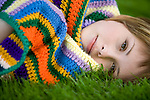 A beautiful girl lies wrapped up in a colorful knit blanket on fresh green grass.