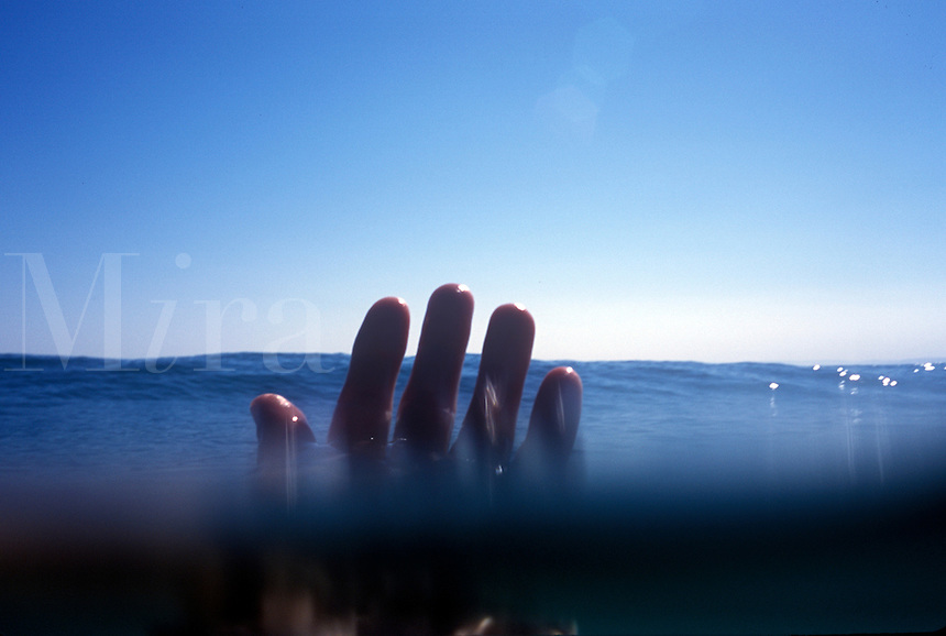 Mans fingertips just above water level..