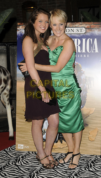 "HELEN FLANAGAN & SALLY WHITTAKER .Coronation Street ""Out Of Africa"" DVD Premiere at Odeon Printworkds Centre, Withy Grove, Manchester, England. .November 4th 2008.full length purple aubergine dress gold trim black clutch bag green silk satin hug embrace .CAP/CAN.©Can Nguyen/Capital Pictures."