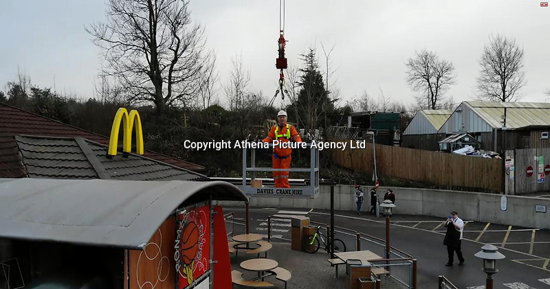"""Pictured: Malcolm Davies in the basket of a crane on his way back after collecting his takeaway from a nearby McDonalds restaurant in Carmarthen, West Wales, UK.<br /> Re: Workers at a crane hire company got creative with their brand new crane which they used it to pick up a McDonald's takeaway in Carmarthen, west Wales, UK.<br /> The 40m Spierings/SK1265-AT6 machine is mostly used for lifting heavy loads of anything up to 10 tonnes.<br /> But instead, they showed off its remarkable precision skills, too, by lifting a man to his lunch break.<br /> Malcolm Davies, the owner of Davies Crane Hire, said they did it for a bit of fun and captured the whole thing on video.<br /> Mr Davies said: """"We phoned McDonald's the day before and they said it was fine.<br /> """"So at 12.30pm, I rang them up to order my food, and said I was on my way. Then I climbed into the crane's basket.<br /> The 40 metre high crane went over the trees, and was lowered right by front of the door of the restaurant. Mr Davies meal was handed over and went back over.<br /> It only took about ten minutes to complete the manouevre and Mr Davies is even seen eating his chips on the way back.<br /> The crane operator sits the top of the crane and was in direct contact via radio the whole time.<br /> """"I had a Big Mac."""" said Mr Davies<br /> """"Staff at McDonald's were loving it, they thought it was brilliant.<br /> The Spierings/SK1265-AT6 crane can lift up to 10 tonnes, has a span of 60 metres (197ft) and can reach a maximum lifting height of 64.2 metres (210ft)."""