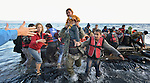 Volunteers carry a child ashore on a beach near Molyvos, on the Greek island of Lesbos, on October 30, 2015, after a group of refugees crossed the Aegean Sea from Turkey in a small overcrowded boat provided by Turkish traffickers to whom the refugees paid huge sums. The refugees were received in Greece by local and international volunteers, then proceeded on their way toward western Europe.