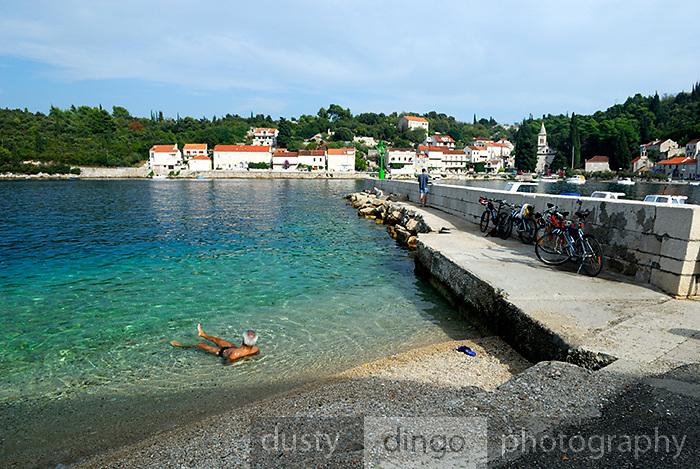 Mature man floating in water at beach, Racisce, island of Korcula, Croatia