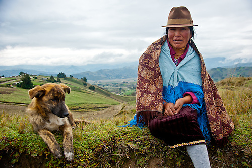 An indigenous woman and her dog rest along the road in the Andes of Ecuador.