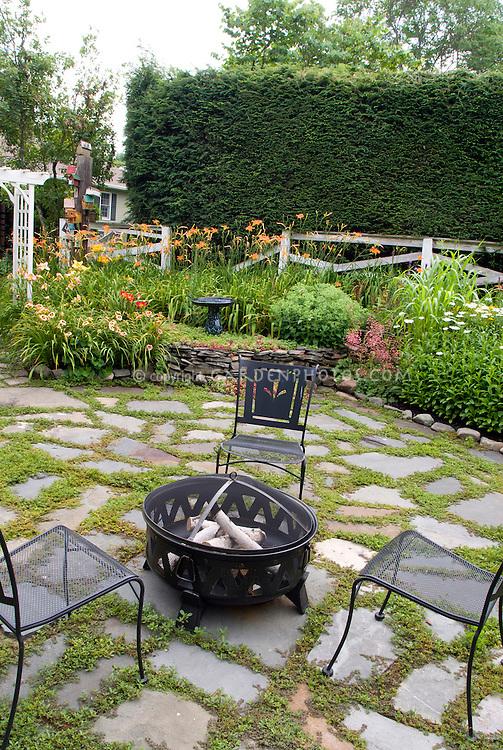 Backyard firepit, chairs, stone patio, Leucanthemum Shasta Daisies, daylilies Hemerocallis, lawn grass, Liatris, trellis, perennial gardens, landscaping the home landscape