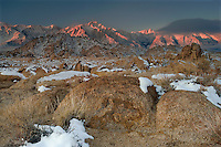 711700285 winter sunrise with snow covered granite boulders in the bureau of land management protected land the alabama hills in the southern section of the eastern sierras with lone pine peak and mount whitneyl in the background in kern county california