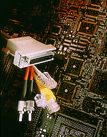 Various connectors used to network computers with circuit board background.