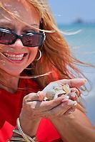 Mareesa DeAngelis, a dance/drama teacher at Bonita Springs School of Arts, scoops up shells on beach along Gulf of Mexico near historic Naples Fishing Pier, Naples, Florida, USA. Photo by Debi Pittman Wilkey