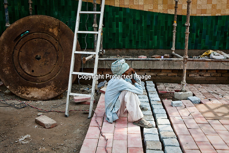 A construction worker takes a break on the pavement outside the Jawahar Lal Nehru metro station in New Delhi, India.