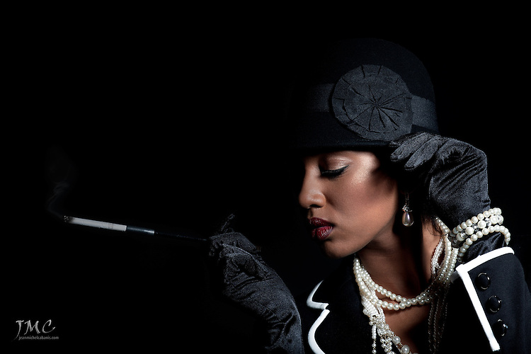 Beautiful fashion model smoking, wearing a black hat, black jacket and pearls