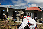 Women clear the grass in front of their new homes built by the Filipino non profit, Gawad Kalinga in Manila, Philippines.