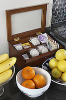 An antique tea caddy is displayed beside bowls of fruit on the granite kitchen work top