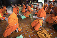 """Chanting Novice Monks at Wat Pan Tao - meaning """"to increase 1,000 times."""" The temple was built in the late fourteenth century and was one of four monastic temples serving the royal temple next door: Wat  Chedi Luang.. The temple's most interesting feature is its teak  wooden wiharn, which was formerly a royal residence but the practice in Lanna was for each new king to built a new palace. The old palaces were often 'recycled' into other uses, especially in temples. Over the main entry door on the east end of the chapel is a large gilded wood carving depicting a peacock flanked by several other animals, some of which are mythical. The peacock was the symbol of the kings of Chiang Mai; this carving has appeared on stamps and other materials celebrating Chiang Mai's 700th anniversary."""