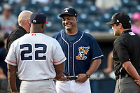 Toledo Mud Hens coach Basilio Cabrera (30) meets with Louisville bats coach Darryl Brinkley (22) and umpires James Rackley (left) and Jansen Visconti (right) prior to the game on May 17, 2017 at Fifth Third Field in Toledo, Ohio. Toledo defeated Louisville 16-2. (Andrew Woolley/Four Seam Images)