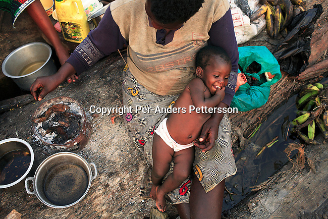 MBANDAKA, DEMOCRATIC REPUBLIC OF CONGO JULY 1: Francesca Mboyo, age 35, cooks skin from a forest antelope for her six children, while traveling on a boat made of big trees on the Congo River on July 1, 2006 outside Mbandaka, Congo, DRC. The boat traveled with about 150 passengers from Bumba to Kinshasa, a journey of about 1300 kilometers. Francesca traveled from a small rural village outside Bumba to the capital, Kinshasa. The Congo River is a lifeline for millions of people, who depend on it for transport and trade. Passengers slept in the open, with their goats, pigs and other animals. Boat travel is the only option for most people along the river as there?s no roads or infrastructure. Very few can afford to fly in a plane to the capital Kinshasa. During the Mobuto era, big boats run by the state company ONATRA dominated the river. These boats had cabins and restaurants etc. All the boats are now private and are mainly barges that transport goods. The crews sell tickets to passengers who travel in very bad conditions. The conditions on the boats often resemble conditions in a refugee camp. Congo is planning to hold general elections by July 2006, the first democratic elections in forty years. The Congolese and the international community are hoping that Congo will finally have piece and the country will be rebuilt..(Photo by Per-Anders Pettersson/Getty Images).
