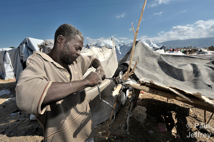 A man uses strips of cloth to fasten together a temporary shelter for his family in a spontaneous camp for quake survivors being established in Croix-des-Bouguets, Haiti, north of the capital Port-au-Prince. Quake survivors continue to move as aftershocks continue, and reports of aid deliveries in one camp will provoke families from other camps to migrate there.