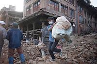 Nepali people carries belongings walks past collapsed houses at Vaktapur, outstrike of Kathmandu, Nepal. May 1, 2015