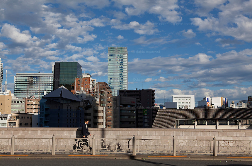 A Japanese salaryman walking on a bridge near Ochanomizu station with Tokyo Skytree and other tall building behind him. Ochanomizu, Tokyo, Japan. Wedneday October 16th 2013