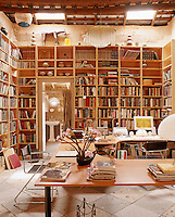 Contemporary wall-to-wall bookcases conceal the original adobe walls in the study
