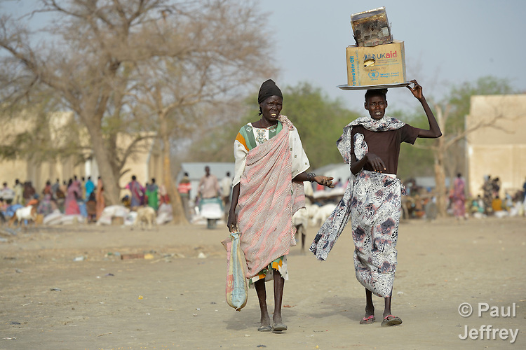 Displaced women walk home after receiving emergency food supplies from the United Nations World Food Program in Agok, a town in the contested Abyei region where tens of thousands of people fled in 2011 after an attack by soldiers and militias from the northern Republic of Sudan on most parts of Abyei. Although the 2005 Comprehensive Peace Agreement called for residents of Abyei--which sits on the border between Sudan and South Sudan--to hold a referendum on whether they wanted to align with the north or the newly independent South Sudan, the government in Khartoum and northern-backed Misseriya nomads, excluded from voting as they only live part of the year in Abyei, blocked the vote and attacked the majority Dinka Ngok population. The African Union has proposed a new peace plan, including a referendum to be held in October 2013, but it has been rejected by the Misseriya and Khartoum. The Catholic parish of Abyei, with support from Caritas South Sudan and other international church partners, has maintained its pastoral presence among the displaced and assisted them with food, shelter, and other relief supplies.