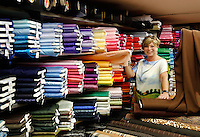 Vrouw laat stoffen zien in een stoffenwinkel