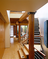 A contemporary central staircase is framed by robust wooden columns in this open plan property