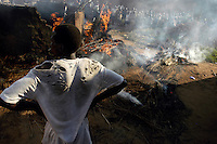 A resident of Palenga camp for the internally displaced (IDP), watched the remains of a hut burn after pushing the rooof off away from other huts to prevent its spread. One man died in the fire. residents of the camps deal with many hazards of close living. (Rick D'Elia)