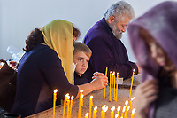 """Nagorno-Karabakh, also known as Artsakh, is a landlocked region in the South Caucasus. Stepanakert is the capital and the largest city of the Republic of Artsakh (better known as Nagorno-Karabakh). Armenian Apostolic Church. """" Saint Jacob """" church. A mother and her son light prayer candles. Nagorno-Karabakh is a disputed territory, internationally recognized as part of Azerbaijan, but most of the region is governed by the Republic of Artsakh (formerly named Nagorno-Karabakh Republic), a de facto independent state with Armenian ethnic population. Since 1994, regular peace talks between Armenia and Azerbaijan mediated by the OSCE Minsk Group have failed to result in a peace treaty.  6.10.2019 © 2019 Didier Ruef"""
