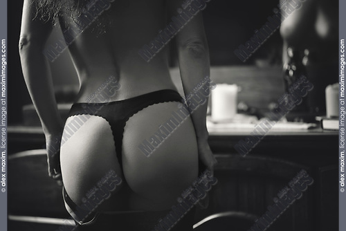 Sensual body parts closeup of woman buttock rear view wearing black underwear dressing up in front of a mirror Black and white