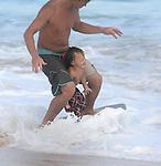 Dad teaches his son how to skim board along Sandy Beach in Hawaii.