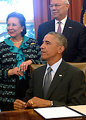 United States President Barack Obama, with America's Promise Alliance Founding Chairman and former US Secretary of State General Colin Powell (R) and current Board Chair Alma Powell (L), listens to a question from the news media after signing the America's Promise Summit Declaration during a ceremony in the Oval Office of the White House in Washington, DC, USA 22 September 2014. President Obama will be the seventh consecutive president to sign the declaration, which calls on Americans to help the youth of America reach their full potential.<br /> Credit: Shawn Thew / Pool via CNP