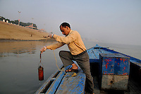 Gopal Pandey (38) collecting water from Ganga at Varanasi for checking the pollution level in it at the laboratory of Sankat Mochan Foundation. He is working as a lab assistant at Sankat MochanFoundation for last 18 years,Sankat Mochan Foundation is an NGO headedby Prof. Vir Vadra Mishra and it works towards making the Ganga water-pollution free in Varanasi. Uttar Pradesh, India.