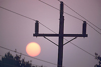 POWER LINES AND SUNSET<br /> Outdoor, above-ground power lines with setting sun in twilight sky.
