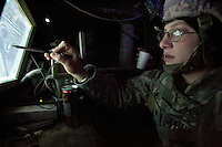 """Specialist Anne Marie Hogancamp, 21 years old from Endicott NY and with Echo Company, 1st Battalion, 506th, 101st airborne Division is verifying  the functionality of the navigation equipment of her truck  while getting ready for a convoy mission at Forward Operating Base Corregidor in Eastern Ramadi, Al Anbar Province, Iraq on Wednesday JAN 18 2006. she has been in the military since April 2004. she is not going to reenlist and once back to civilian life she will study  to become a massage therapist and will go to business college  . when asked why  did she think i Iraq she answered: """" As an American i feel a sense of duty to protect and uphold the freedom of not only my family and friends, but of all my fellow Americans back home. Many before me fought for the same reason. I respect and thank them for that. I miss my family and friends yet knowing they can sleep peacefully in their beds. Not having to worry gives me the most pride. Knowing they are proud of me and of what I'm doing over here makes it easier to do my job, and sets my mind at ease""""."""