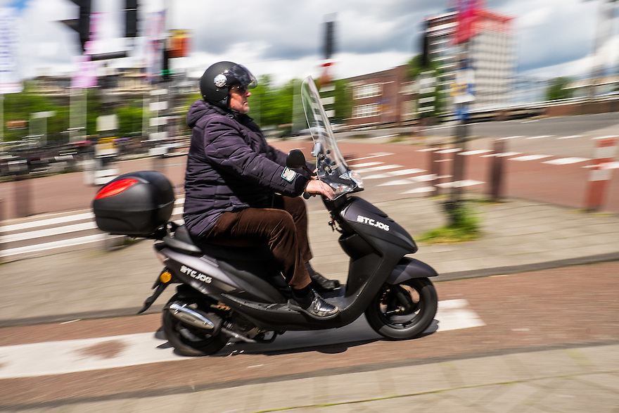 Nederland, Amsterdam, 30 mei 2015<br /> Scooter op fietspad in het centraum van de stad.  Scooters stoten heel veel fijn stof uit en zijn enorm ongezond voor de stadsbewoners. De luchtkwaliteit wordt ernstig aangetast door scooters en bromfietsen of snorfietsn. <br /> Dit is waarschijnlijk een snorfiets of snorscooter, want er is geen geel plaatje zichtbaar. De man draagt desondanks een helm, maar dat is eigenlijk niet nodig.<br /> <br /> Foto: Michiel Wijnbergh