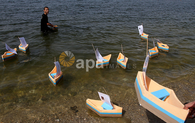 Palestinian youths push paper boats out to sea along the shores of the Mediterranean as they rally to demand the lifting of an Israeli blockade on the Gaza Strip, on October 17, 2010, a day after a delegation of the Elders group of retired world figures visited the Hamas-ruled Gaza Strip and called Israeli restrictions on the Palestinian enclave both illegal and an obstacle to peace . Photo by Ashraf Amra