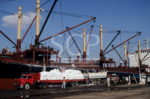 Buenos Aires, Argentina. Port with white sacks being unloaded onto a truck by hand from a cargo ship.